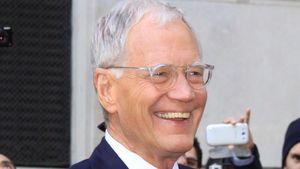 David Letterman lachend mit Händen in den Hosentaschen