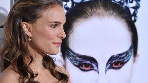 """Natalie Portman vor einem """"Black Swan""""-Plakat"""