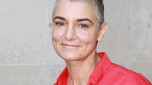 Sinead O'Connor mit roter Bluse und coffee to go