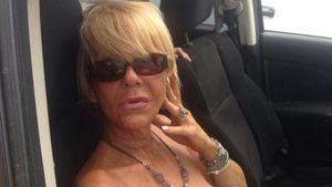 Tanning Mom sitzt mit Sonnenbrille im Auto