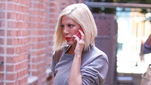Tori Spelling läuft mit Handy am Ohr