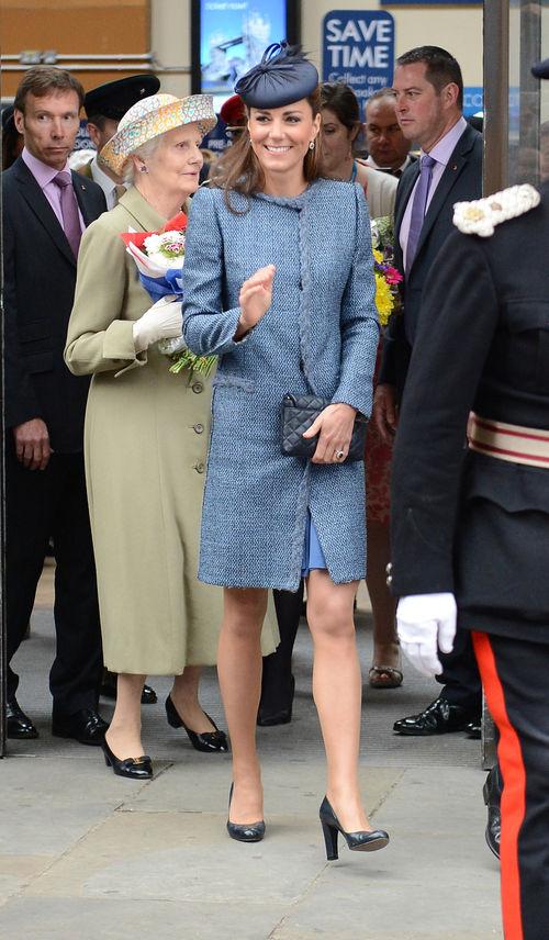 Herzogin Kate hält ihre Clutch vor ihren Bauch