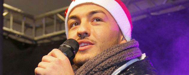 Ardian Bujupi mit Mütze auf der Bühne