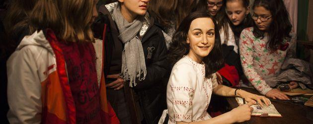Besucher mit der Wachsfigur von Anne Frank