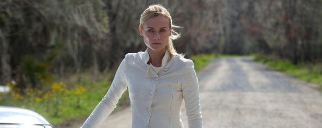 Diane Kruger in einem weißen Overall neben einem Auto