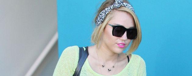 Miley Cyrus trägt einen lockeren gelben Pulli zu schwarzen Mini-Shorts