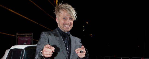 Ross posiert vor einem pinken Cadillac