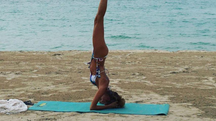 Heißes Workout: Cathy Hummels steht am Strand Kopf