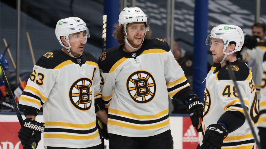 David Pastrnak (M.) mit Teamkollegen der Boston Bruins