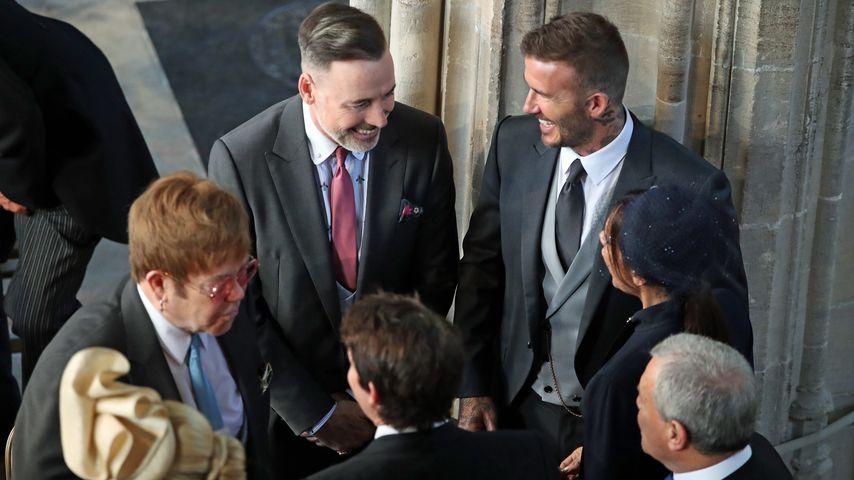 David und Victoria Beckham (rechts) reden mit Sir Elton John (li.) und David Furnish (Mitte)
