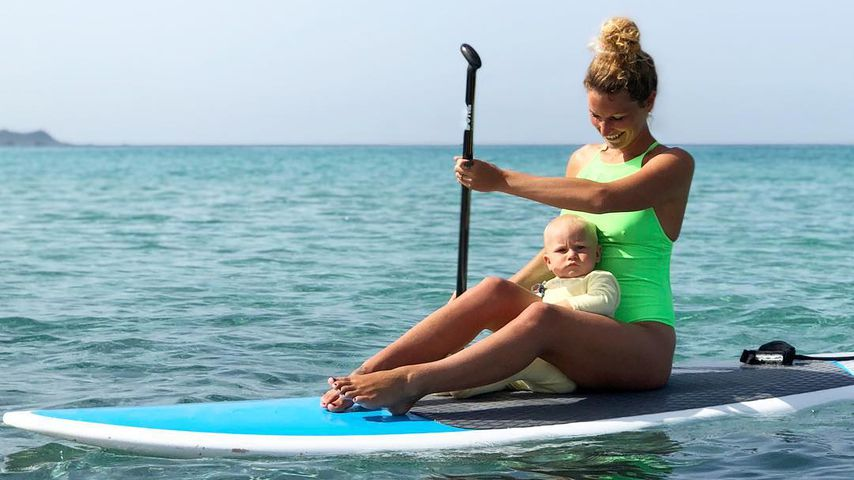 Janni Hönscheid und Emil-Ocean auf einem Surfbrett
