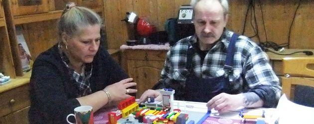 Die Wollnys: Silvia und Dieter am Tisch vor einem Spielzeug-Modell